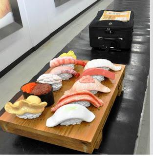asahi shimbun A fake Toyama Bay-style sushi set takes a ride on the baggage carousel at Toyama Airport. (Yuji Shimoyama)